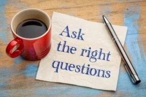 Coffee cup and ask the right questions sign